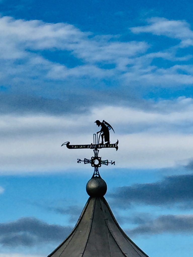 picture of the old father time windvane on top of the bandstand in durham, with blue sky to the background