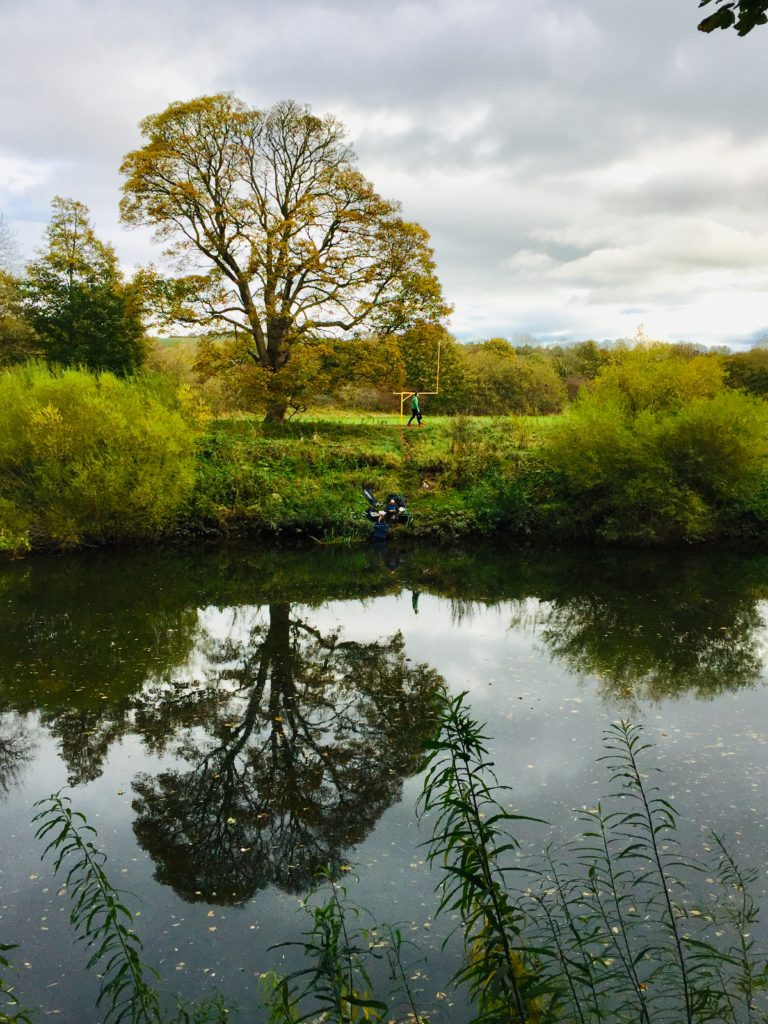 picture of a fisherman on the river wear under a tree that is reflected in the water