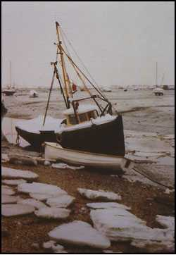 photograph of a boat stranded and surrounded by ice in a harbour in southern england ring the winter of 1962-63