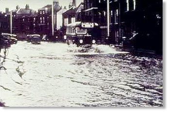 A picture of a bus driving through water during the flooding of 1947