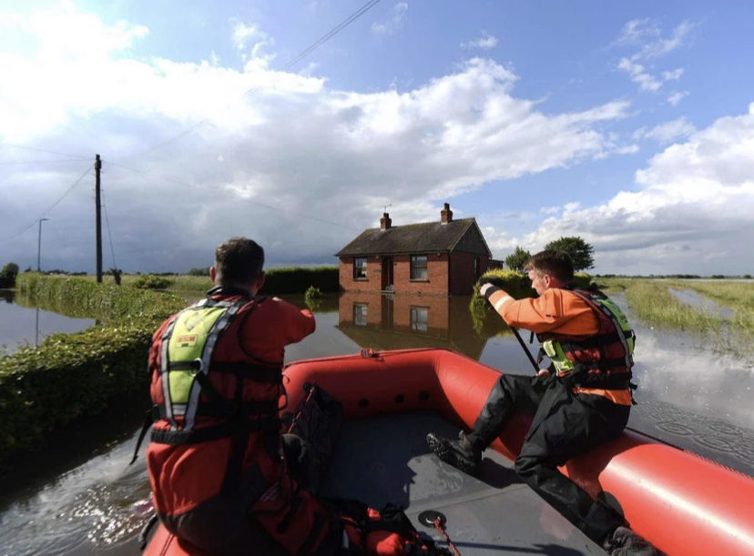 rescuers paddling through flood water after floods in June 2019